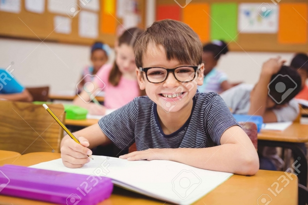 43914315-Little-boy-working-at-his-desk-in-class-at-the-elementary-school-Stock-Photo